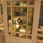 An interior door design  with simple pattern stained glass panel in top middle of door