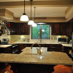 Bianco Romano granite countertop for kitchen simple clean kitchen brown wooden furniture classic hanging lamps