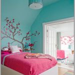 Blue wall paint color with beautiful wall art white bed with deep pink bed linen and white pillows multi colors bedroom rug with strips pattern wood floors blue pendant lamp