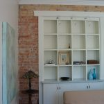 Built In Cabinets And Shelves Red Brick Wall System  A Round Table As The Corner Decoration