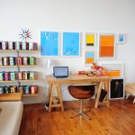 Cheerful and colorful office decorating idea wall shelving unit with colorful boxes a sofa with beautiful throw pillows wood office desk a unique office chair colorful canvas boards as wall arts