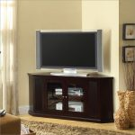 Corner cabinet as TV console with glass door some media players a flat TV light brown wool rug beautiful rattan vases as corner decoration units