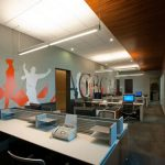 Creative office decoration idea with colorful mural arts large white neon light fixtures white modern office tables