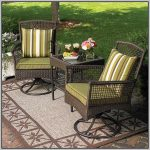 Darker stained rattan chairs for outdoor with green cushions and strip pattern pillows beautiful rug for outdoor with flower patterns a rattan table tray