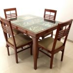 Displayed glass top dining table with wood dining chairs with soft brown cushions