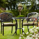 Elegant black outdoor armchairs with cushions small round metal table in black stain