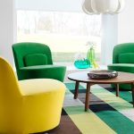 Ergonomic chairs in bright yellow and green colors colorful strips area rug white pendant lamp wood round table