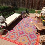 Fab Habitat colorful motives recycled plastic outdoor rugs recycled furniture bold brown wooden sofa backyard patio natural tile floor flower pots accent green grass