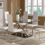 Frameless glass dining table with metal legs and black metal base six white dining chairs soft grey area rug