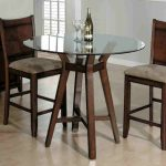 Frameless round glass top table with a pair of dark rustic dining chairs