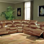 Home theater style sectional sofa with brown leather cover several painting arts as wall decorations modern area rug