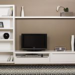 L shaped ikea white tv stand with storage and wall rack and cream painted wlal and honey comb patterned area rug