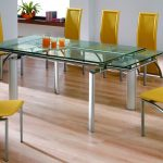 Large and narrow glass top dining table with metal legs modern yellow dining chairs in unique design