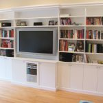 Large Built In Cabinets And Bookshelves In White Color Wood Flooring Idea