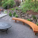 Larger curved bench made of wooden for patio a round patio table with firepit in the center