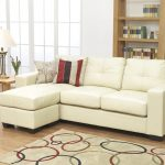 Light cream L shape sectional sofa with decortaive pillows an area rug with colorful circle patterns wooden side table with table lamp wooden bookshelf