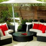 Luxurious black rattan sofas with white cushions red and white throw pillows round black table with transparent glass top large white umbrella as patio roof