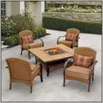 Rattan patio chairs with brown cushions and small throw pillows outdoor table with fire pit in the center