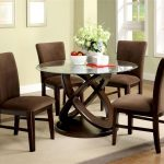 Round glass top table with artistic wood legs elegant brown dining chairs white rug with bold grey border lines