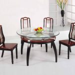 Round glass top table with round additional shelf made of wooden luxurious chairs for dining room