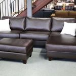 Sectional sofawith single chaise white throw pillows an ottoman with black leather material