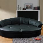 Semi circular sectional sofa in black grey shag rug idea wood floor idea a standing lamp a single wall shelf unit for displaying books picture frame and single chandeliers