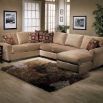 Simple U shape sectionals in light brown beautiful throw pillows smaller wool rug in neutral color schemes a black stained wood side table with mini table lamp