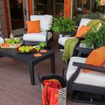 Simple black stained wood chairs with white cushions and orange throw pillows for patio wood planks patio floors