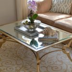 Stunning glass top table with gold toned iron frame and legs light brown sofa with decorative pillow a classic rug idea with beautiful pattern