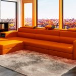 Top floor living room bold orange recliners soft fur carpet wooden bookshelf abstract wall painting