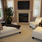 Two armless white chairs with white throw pillows a white sidebed furniture with darker pillow and deep brown blanket black round side table with table lamp a modern fireplace mounted TV set