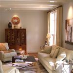 Wendt Design Group interior decorator Houston Texas for charming traditional living room with beige sectional sofa and antique motive wooden cabinet