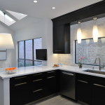 Wendt Design Group interior designer Houston for modern sleek black and white kitchen and dining space with big classic white ceiling lamp and pink flower