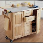 Wood kitchen cart with half way metal and half way wood top drawer system and cabinets and also wheels