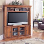 Wooden corner TV cabinet with additional upper shelf in modern rustic style a big flat TV classic area rug wood floors idea an arm chair with black stained wood side table with table lamp