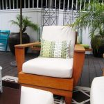 Wooden outdoor chair with white cushion and throw pillow