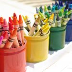 a row of colored pencil holder idea in red yellow green blue and purple color in can shaped with unique pencil design