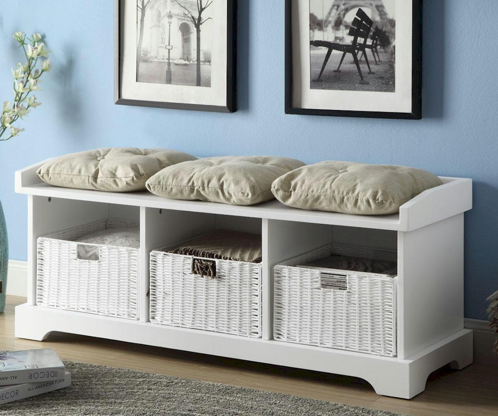 A White Wooden Bench Design With Rattan Storage Bo Underneath And Three Throw Pillows
