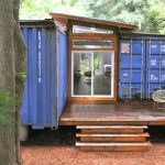 adorable blue shipping container shed design with glass door and wooden deck porch with round chair and staircase