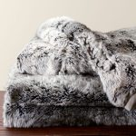 adorable gray faux sheepskin throw design like fox skin on wooden floor