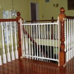 adorable interior design with yellow painted wall and wooden floor and white staircase with wooden railing and white metal baby gate for top stairs