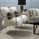adorable interior with white seating and gray area rug with wite faux sheepskin throw and chevron patterned cushions