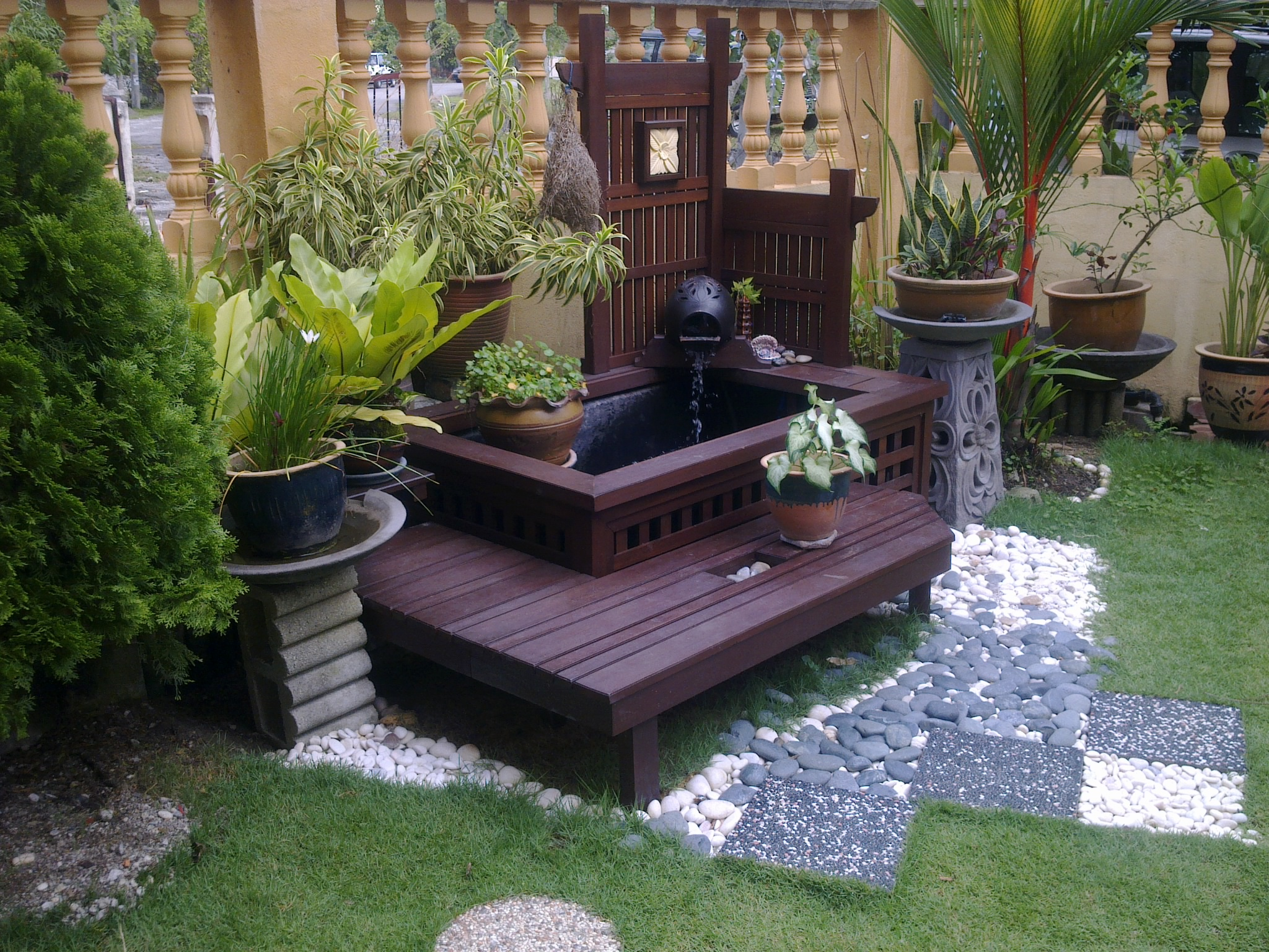 Adorable Simple Front Yard Fountains Design With Wooden Deck In Dark Tone Potted Plants And