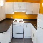 adorable small kitchen design in u shape with brown countertop and yellow backsplash and upper cabinet and gray tile flooring and wall lamp