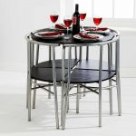 adorable space saver dining set in black finishing  in round shape decorated with space saving chair with steel leg and elegant dishes and flatware