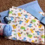 animal patterned cloth to make baby quilt with blue accent and stitching tool