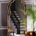 arched style luxurious beveled floor mirror design on gray wall with golden potted plants