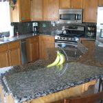 beautiful baltic brown granite countertop for sleek looking kitchen with brown wooden cabinet