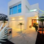 beautiful white small lot house idea with two storey with large patio and some plants and open plan