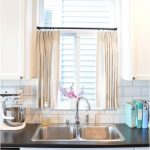 beige half window curtains decorated on kitchen windows above the sink and black coutertop plus subway tiles for backsplash